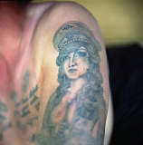 "A tattoo depicting a woman in a Nazi cap showing off her breasts. During Soviet times, tattooed Nazi symbols were very popular among criminals as they symbolised their resistance against the ""system""."