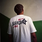 A man poses for picture in a T-shirt with the logo of a local radio station that broadcasts criminal songs - the so-called shanson.