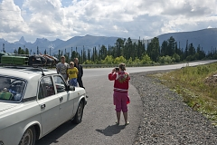 Tourists take a picture during a stop on the scenic M-54 highway - basically the only road that connects Tuva with the rest of Russia. The rugged Yergak-Targak-Taiga ridge - part of Sayan Mountains - is visible in the background. Tuva lies behind this ridge.