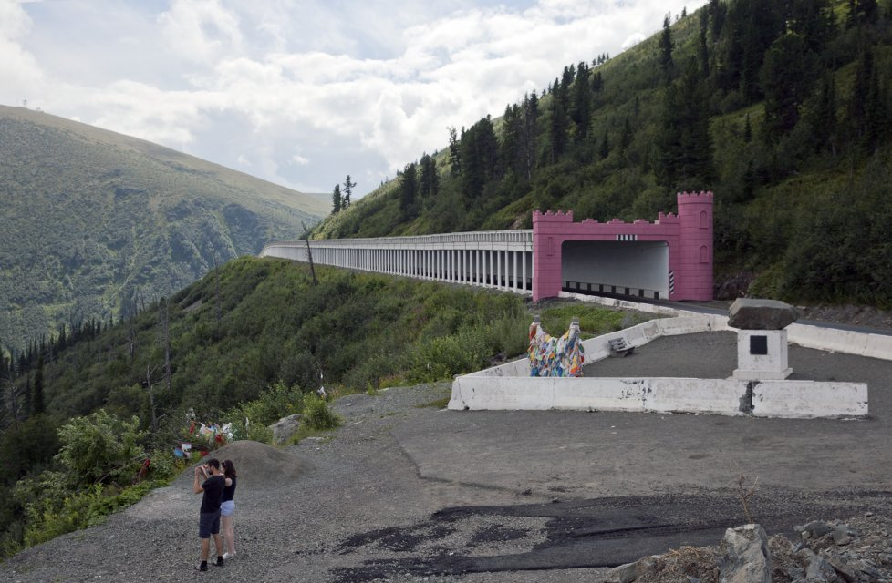 Tourists take a picture near The Shelf - an anti-avalanche tunnel at Buibinsky Pass in the Sayan Mountains that separate Tuva from the neighboring Krasnoyask Territory. A prominent Russian politician Lt Gen Alexander Lebed who came third in the 1996 presidential election and later became governor of Krasnoyask Territory, died in a helicopter crash here in 2002.