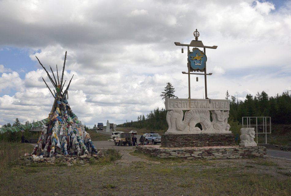 Entrance sign that reads Republic of Tuva in Russian and depicts a dragon and the region's seal (a yellow horseman); to the left is an ovaa - a Tuvan sanctuary made of poles with prayer ribbons attached to them. Before the Chinese Qing Empire, of which Tuva was made part in the 18th century, collapsed in 1912, the Russian-Chinese border ran here.