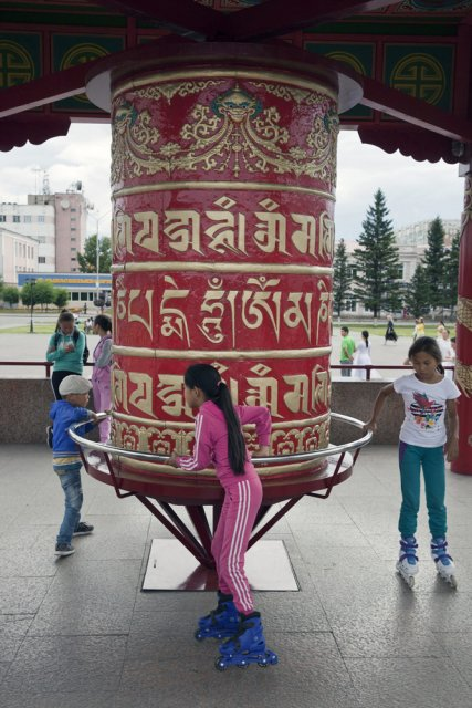 "Kids playing with the Buddhist prayer wheel in the Tuvan capital Kyzyl's main square - the Arat Square. Arat is Tuvan for ""stock farmer"". After Tuva has formally joined the Soviet Union in 1944, all monks were prosecuted and temples completely destroyed to help Communist ideology take hold instead. After the breakup of the Soviet Union, Buddhism has seen a controversial revival in Tuva, although it's the religion's power consolidating potential rather than its true meaning that's being prioritized by the authorities all over Russia irrespective of whether it's Christianity, Islam or Buddhism."