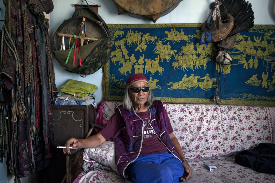 "Nikolay Öorzhak, a shaman, in his Kyzyl office. Trained as a stage designer in Moscow, he later served as art director of the Tuvan National Theater in Kyzyl. In 1990, he founded the first shaman community in Tuva. ""You can understand shamanism only if you become a shaman yourself. Shamanism is not a religion"", he says, ""it is a foundation of all religions. God is the energy of the universe, all else - Buddha, Christ - are just images"". Mr Oorzhak says he receives many Western visitors, mostly psychologists."