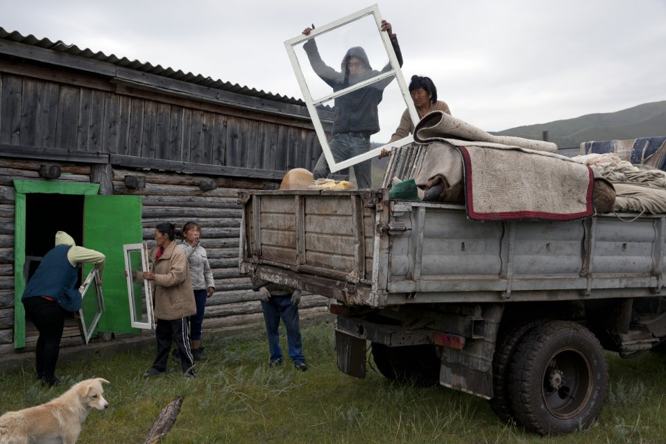 Villagers and members of Bandan family unload their truck at a community warehouse in Kachyk - an isolated village in southeastern Tuva bordering Mongolia - after returning from the yearly stock farmers' festival Naadym. This community won the Best Yurt competition and because they prepared and made that yurt together, the prize - 90,000 RUB (ca. $1,400) - will be shared according to everyone's contribution.
