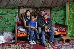"Alimaa and Ertine Bandan, 28 and 29, with their sons Bimdorch, 9, and Sayin-Belek, 3, posing for picture in their family yurt. In summer, they live in this yurt in the Kachyk river valley - a remote area in southeastern Tuva bordering Mongolia. In fall, they return to the nearest big village Naryn - some 100 km away - where they also have a house and where Sayim-Belek goes to school. Together with Ertine's parents and other relatives, the Bandan family keeps more than 2,000 stock - mostly sheep, cows and horses. They have about 80 hectares of private land and rent more land for a winter station. Alimaa also makes traditional Tuvan skin and wool clothes mostly for family use. Says Ertine: ""I like it more when we are here in the valley, living in our yurt, I am my own boss here, there is no authority above. We all know each other here and live together peacefully""."
