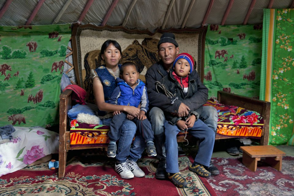 "Alimaa and Ertine Bandan, 28 and 29, with their sons Bimdorch, 9, and Sayin-Belek, 3, posing for picture in their family yurt. In summer they live in this yurt in the Kachyk river valley - a remote area in southeastern Tuva bordering Mongolia. In fall, they return to the nearest big village Naryn - some 100 km away - where they also have a house and where Sayim-Belek goes to school. Together with Ertine's parents and other relatives, the Bandan family keeps more than 2,000 stock - mostly sheep, cows and horses. They have about 80 hectares of private land and rent more land for a winter station. Alimaa also makes traditional Tuvan skin and wool clothes mostly for family use. Says Ertine: ""I like it more when we are here in the valley, living in our yurt, I am my own boss here, there is no authority above. We all know each other here and live together peacefully""."