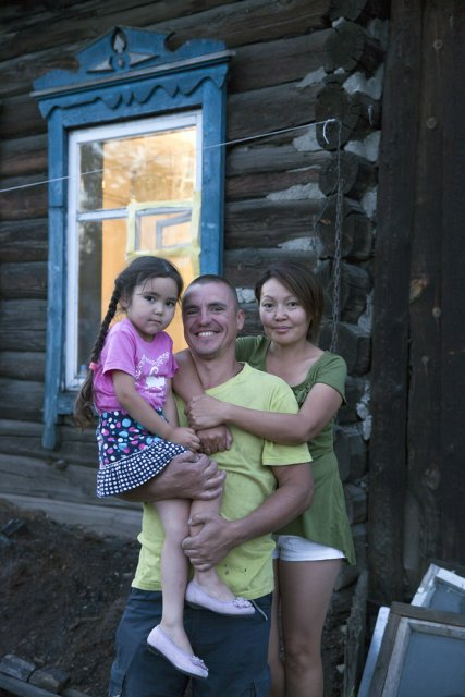 "Filipp (41) and Shonchalay (37) Kozenyuk with their daughter Daria pose for picture in front of their house in central Kyzyl - the Tuvan capital. More than a 100 years since Tuva first became a Russian protectorate and even more years since first Russian settlers began penetrating in the isolated Tuva, mixed marriages are still a rare sight here. Filipp was born in Hungary, the son of a Soviet army officer. Trained as a psychologist in Moscow, he worked as a chef at a Japanese restaurant in the Russian capital where he met Shonchalay, a native of a Tuvan village who failed her exams at a Moscow university but stayed on and went to work as a waitress at that Japanese restaurant (in early 2000s, these establishments hired mostly 'Asian-looking' Russian minorities including Tuvans, Kalmyks, Buryats and Yakuts). Filipp's parents were not really happy with his marriage (because of Shonchalay's origin) until a story that happened to them some years later. Filipp was invited by a friend to work as a chef in Goa, India, where he then opened his own food joint but then got involved in some semi-legal activities, was jailed for a few months, then released on bail and fled India with a forged passport, first going to Nepal, then Tibet, China, and finally finding himself in Mongolia from where he was helped by Shonchalay's Mongolian relatives to illegally cross the Russian-Mongolian border in Tuva. The couple and their two kids have finally settled in Kyzyl ever since. Of Russian-Tuvan interethnic relations Shonchalay recalls that during late Soviet era, most Tuvans faced daily discrimination at almost every step - from getting jobs and housing to buying bus tickets or being served at shops - except for the very top positions in the regional government, most well-paying jobs were held by ethnic Russians and the capital Kyzyl was considered a ""Russian"" city - rural Tuvans being kept away. When the Soviet economy collapsed, Tuva's Russian community has shrank significantly, and this discrimination is now long gone although tensions can still be felt. Ethnic Russians and Tuvans form two distinct communities that rarely mix up and only interact out of necessity."