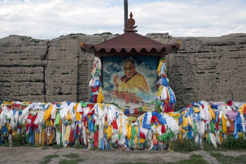 A portrait of Dalai Lama with prayer ribbons and blessing scarves at what remains from a 1908 Buddhist sanctuary Ustuu-Khure outside Chadan in western Tuva, which at the time of its completion was an important center of the Tuvan nation-building: the first Tuvan alphabet was developed here and the first coin minted. The monastery was built at the order of the local noyon (tribal ruler) Khaidyp - the adoptive father of the future founder and first prime minister of independent Tuva Mongush Buyan-Badirgi. After Buyan-Badirgi was arrested and murdered after a coup staged by his Communist-leaning subordinates, this monastery was destroyed and all monks prosecuted, some of them executed. The monastery was revived in 2008 with the support of the then Emergencies MInister and a native of Chadan Sergei Shoigu - Russia's current defense minister.