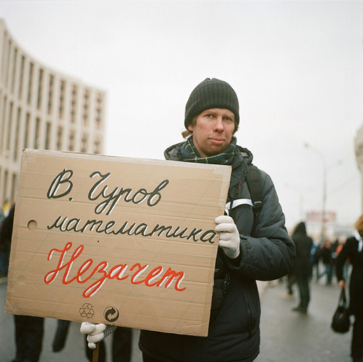 Pavel, engineer, with a sign that may be loosely translated as 'Churov, you failed your maths exam' (Vladimir Churov is the chairman of the Central Election Commission, accused of massive fraud during the last parliamentary elections)